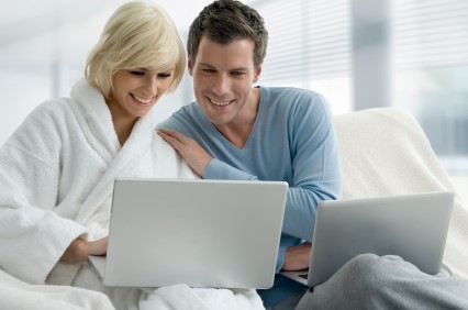 Couple looking at laptops.