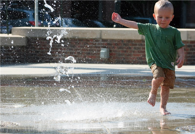 Kid playing in park fountain