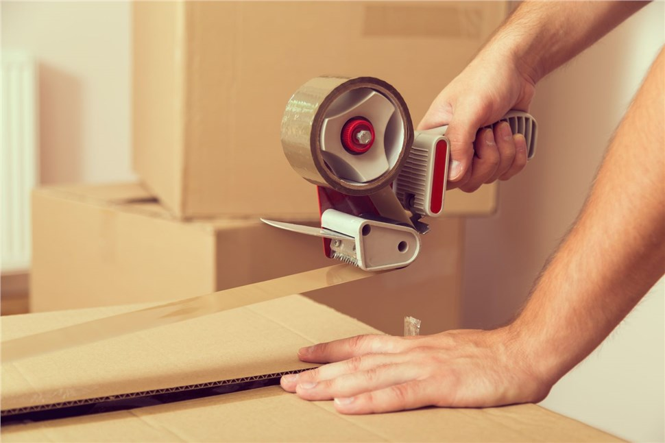 person taping packed moving box
