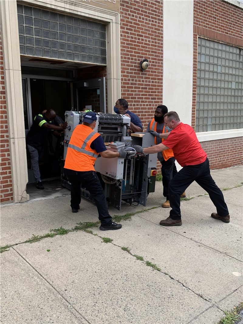 Team moving a printing press during an office relocation in Poughkeepsie