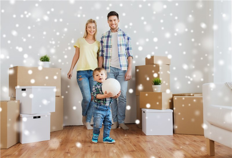 young family with packing boxes and fake snow