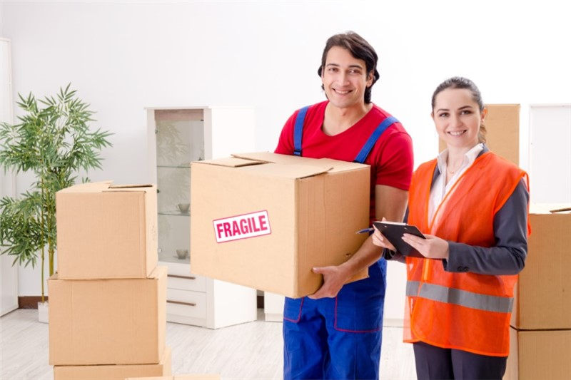 Movers holding box containing fragile items
