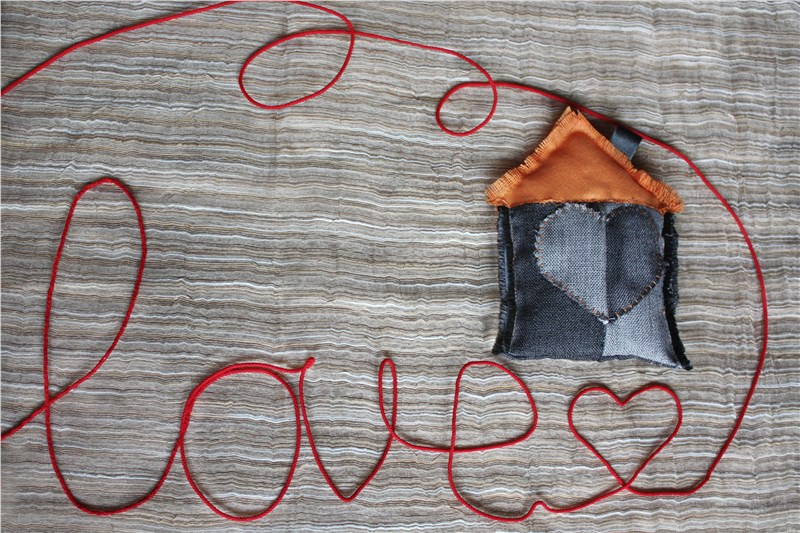 "The word ""love"" is laid out of a red thread. The house is a symbol of housewarming."