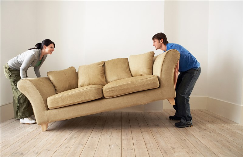 a man and woman attempting to lift a sofa