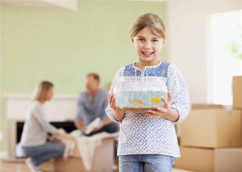 young girl holding fish bowl in new home