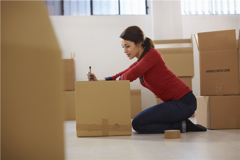 woman packing heavy items in boxes