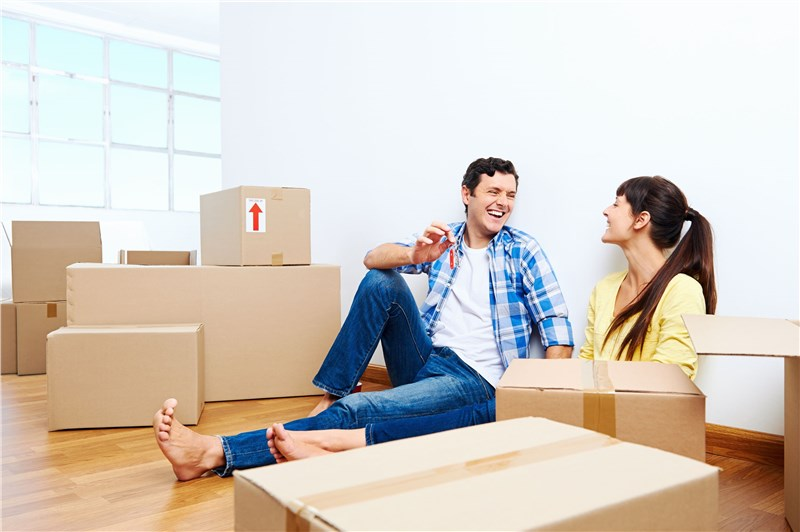 man and woman surrounded by moving boxes